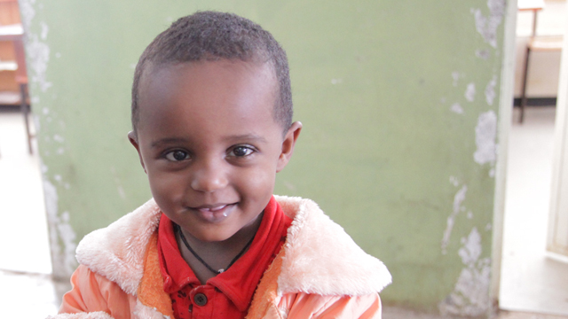 Young African boy smiling for the camera.