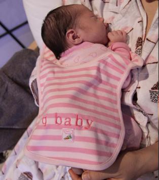 "A newborn baby wearing a ""q baby"" bib."