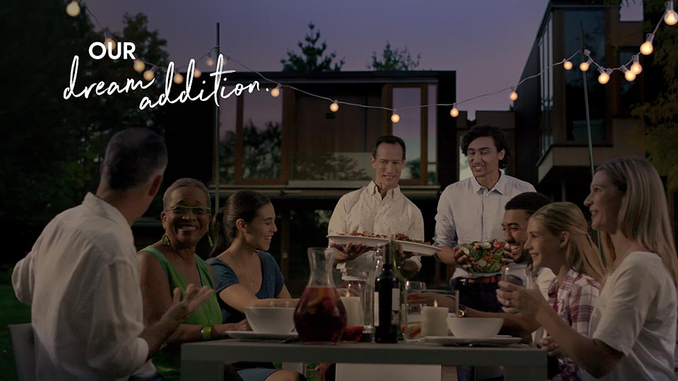 """A couple serves guests in their backyard. Everyone is smiling and enjoying themselves on this summer's night. The backyard is beautiful with fairy lights throughout. Text says """"our dream addition""""."""