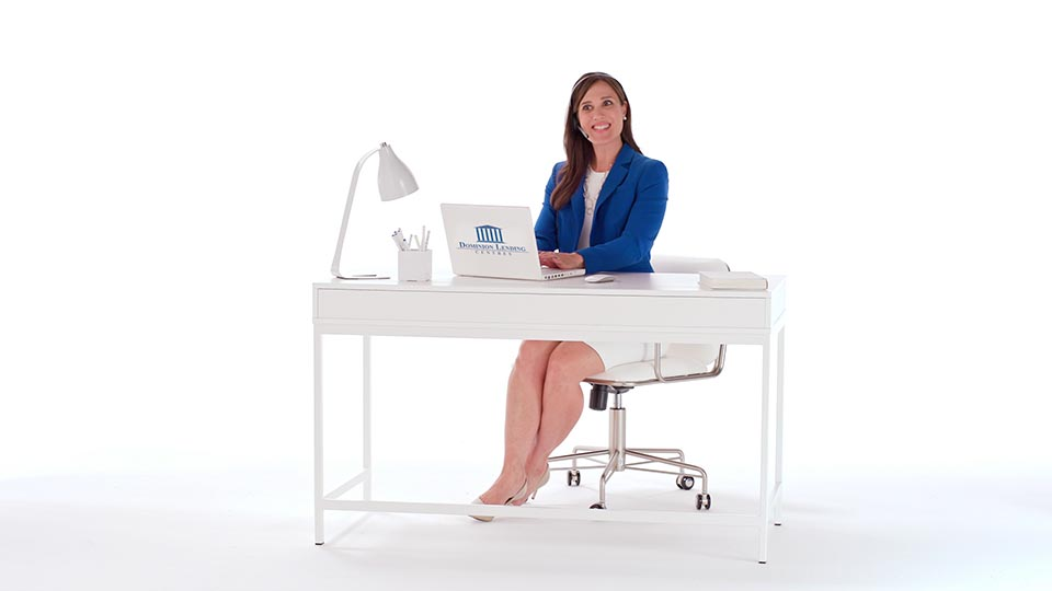A woman in blue sits at a desk in white space, surrounded by white props.