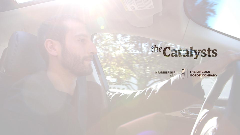 """The opening frame of this series, featuring a man behind the wheel of a Lincoln. The test says """"the catalysts"""" with a Lincoln logo"""