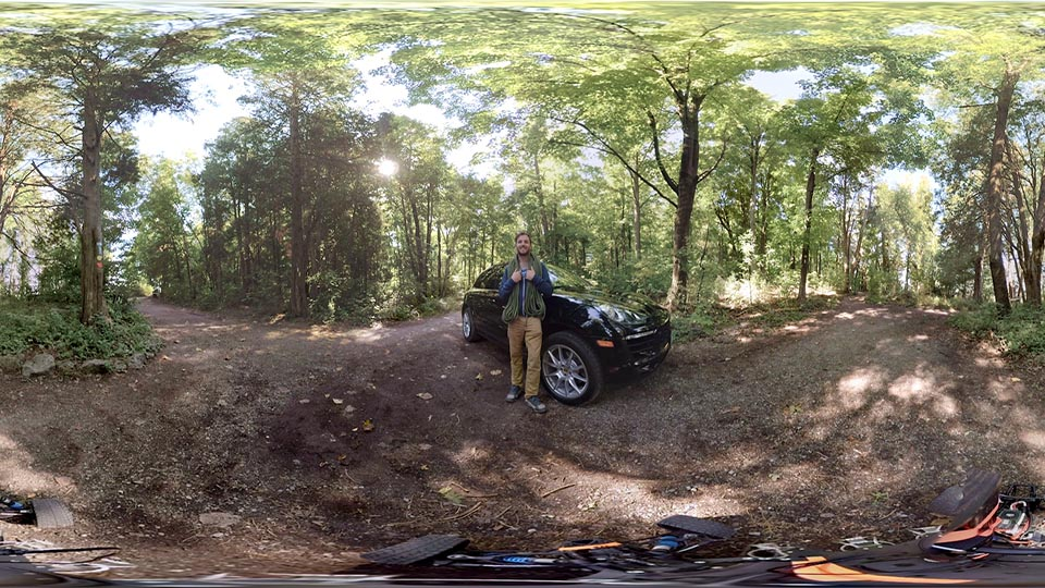 A young man stands in front of a Porsche car in the middle of a forest.