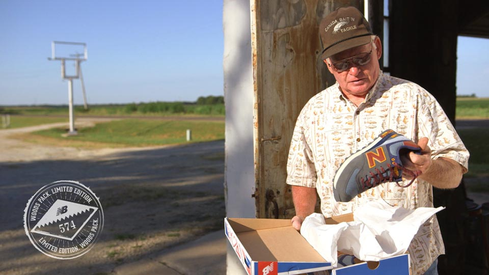 A farmer holds up his new pair of New Balance shoes.
