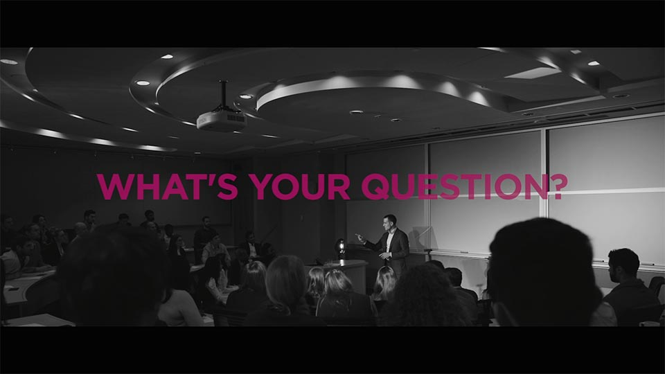 """A shot of Som speaking to students in a classroom. Text: """"What's your question""""?"""