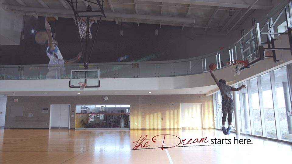 """A young YMCA basketball player slam dunks with the text """"The dream starts here""""."""