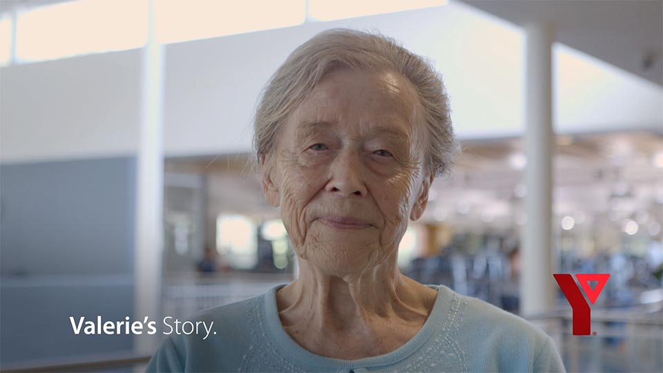 Valerie, a 90-year old YMCA member looks directly into the camera with a smile.