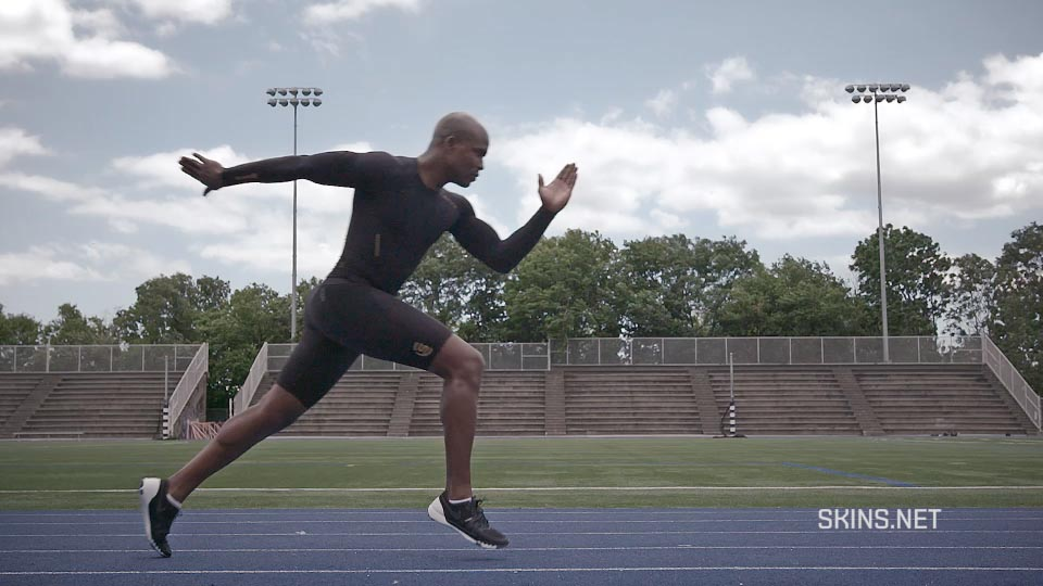 A sprinter in SKINS athletic wear is caught in a mid-start stride in a large outdoor track stadium.