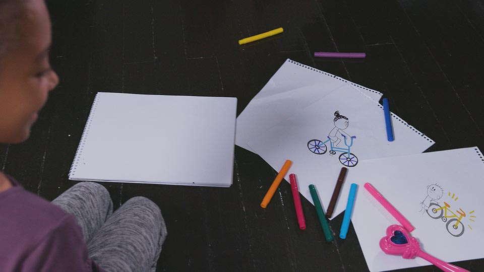 A child sits on the floor while her drawings of two kids on bikes animates right in front of her eyes.