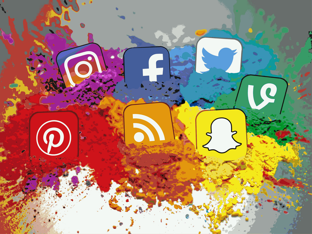 7 social channel icons in a rainbow of colours with exploding paint. Illustration.
