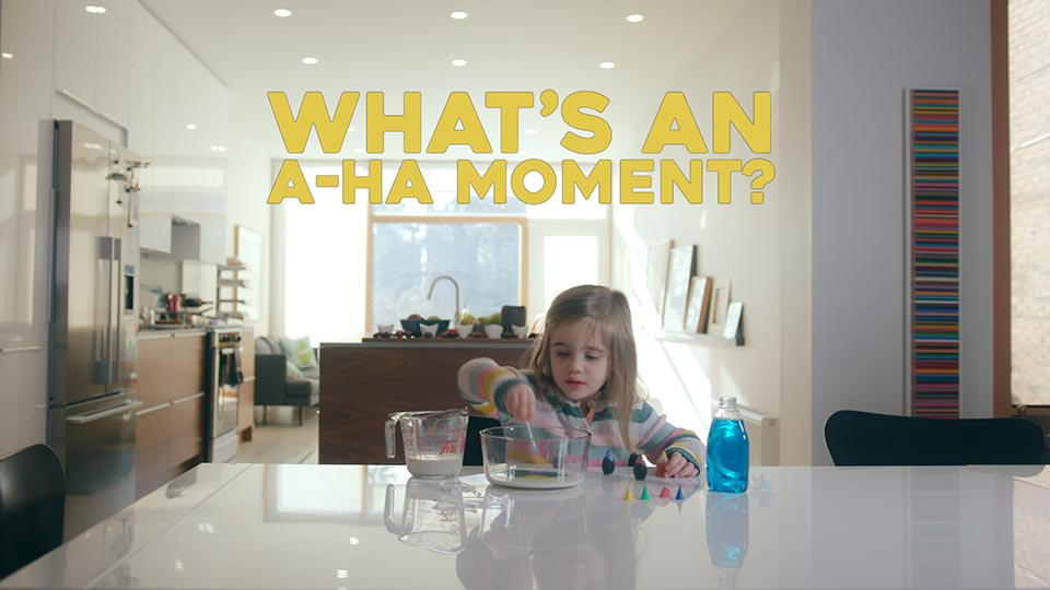 "A little girl places a Q-tip into a bowl of milk and food colouring - conducting a small science experiment. She is in a big open kitchen. Above her is the text ""What's an a-ha moment?"""