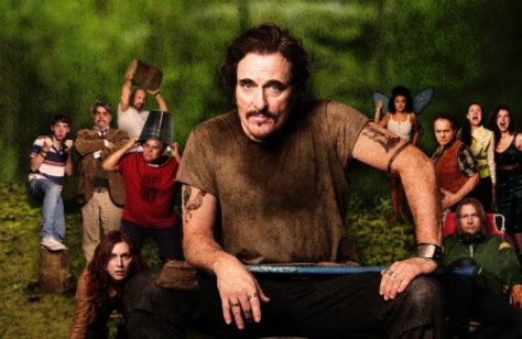 Canadian icon Kim Coates poses for a theatre poster on a wooden stump with an axe in his hand. Behind him are the 13 additional members of the cast, in full party mode. The setting around them is a forest.